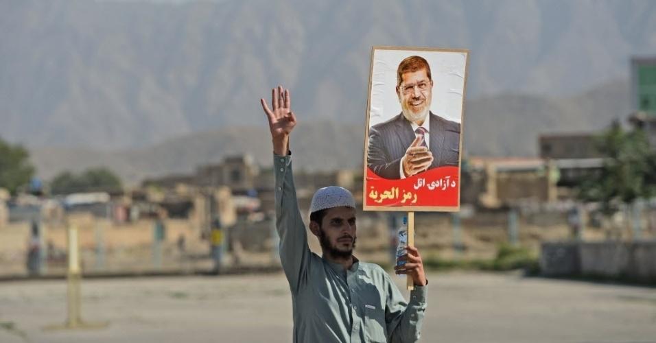 23.ago.2013 - Afegãos segura placa em apoio ao presidente egípcio deposto Mohamed Mursi, durante protesto em Kabul, no Afeganistão, nesta sexta-feira (23). Cerca de 2.500 manifestantes participaram do ato, logo após as orações de sexta-feira