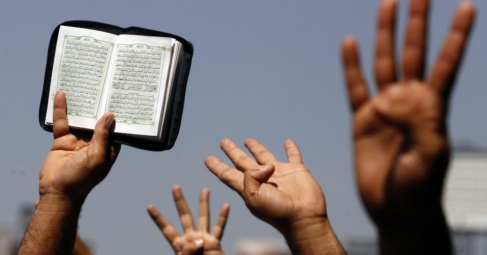 23.ago.2013 - Apoiadores da Irmandade Muçulmana e do presidente egípcio deposto Mohamed Mursi seguram o Alcorão e fazem o gesto