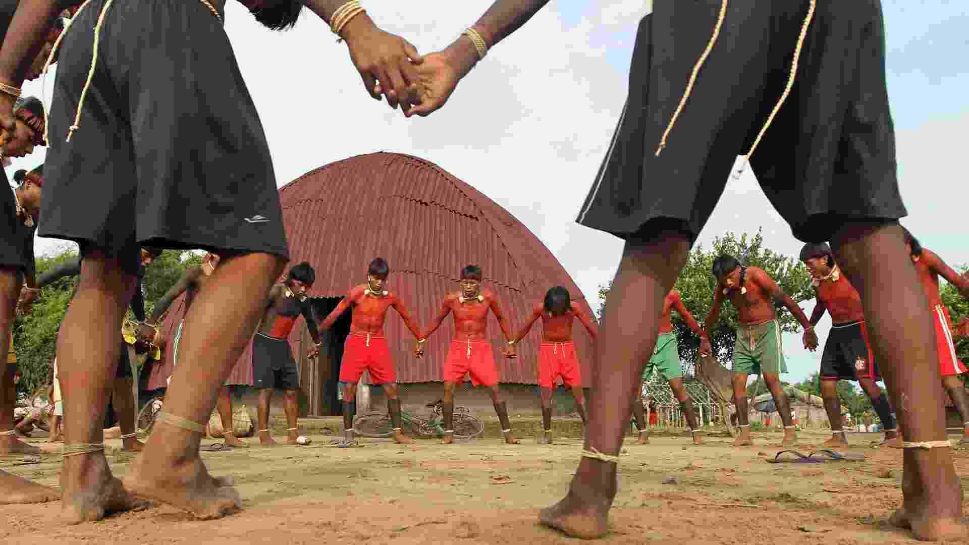 """23.ago.2013 - Índios dançam em ritual na reserva xavante Marãiwatsédé, em Mato Grosso, que fica a 600 quilômetros de distância de Brasília (DF), em registro de fevereiro passado. A Funai (Fundação Nacional do Índio) afirmou que imagens de satélite captaram mais de 400 incêndios iniciados apenas nesta semana, provavelmente como uma """"retaliação  contra a desintrusão"""" - cerca de 7.000 moradores não-índios tiveram de deixar a área sem indenização, agravando a tensão entre índios e fazendeiros - Paulo Whitaker/Reuters"""