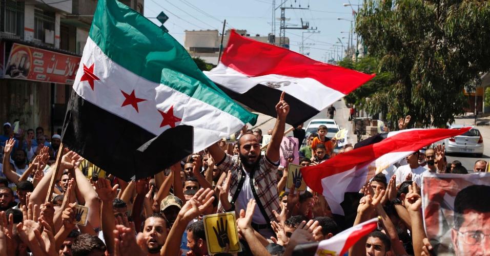 23.ago.2013 - Palestinos gritam palavras de ordem enquanto erguem bandeiras da oposição Síria e do Egito, durante protesto em apoio ao presidente egípcio deposto Mohamed Mursi e contra o mandatário Sírio, Bashar al-Assad, no centro da Faixa de Gaza, nesta sexta-feira (23)