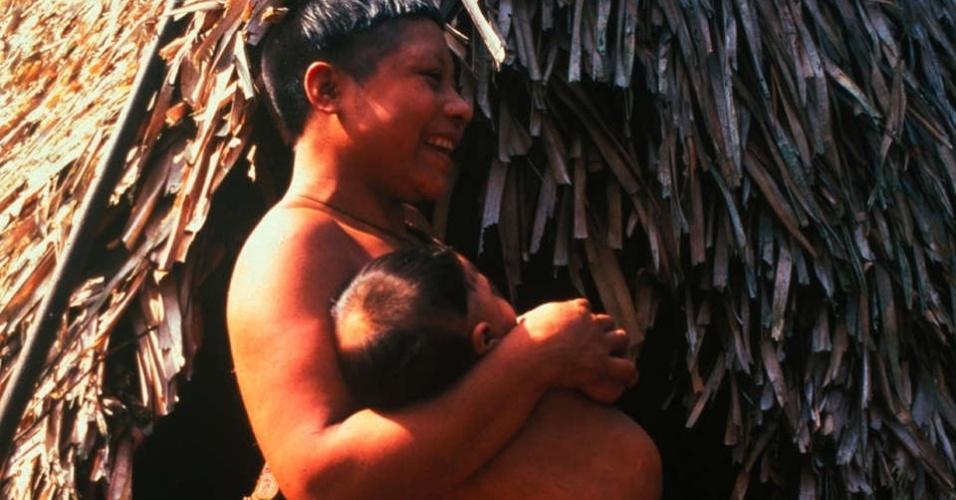 23.ago.2013 - Mulher da etnia Korubo carrega seu filho no colo em encontro amigável com não-indígenas conduzido por Sydney Possuelo, ex-presidente da Funai (Fundação Nacional do Índio), no Vale do Javari, no Amazonas, região próxima à fronteira com o Peru, em 1997