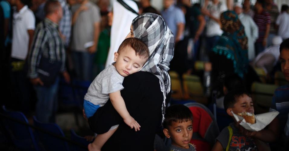 24.ago.13 - Palestina carrega o filho enquanto espera neste sábado (24) para atravessar a fronteira entre a Faixa de Gaza e o Egito, na cidade de Rafah. O Egito reabriu o posto de imigração após quatro dias de interdição desde a morte de pelo menos 24 policiais no Sinai, no mais sangrento atentado contra as forças da ordem em anos. O país enfrenta uma crise política acompanhada de uma escalada de violência que já deixou mais de 800 mortos