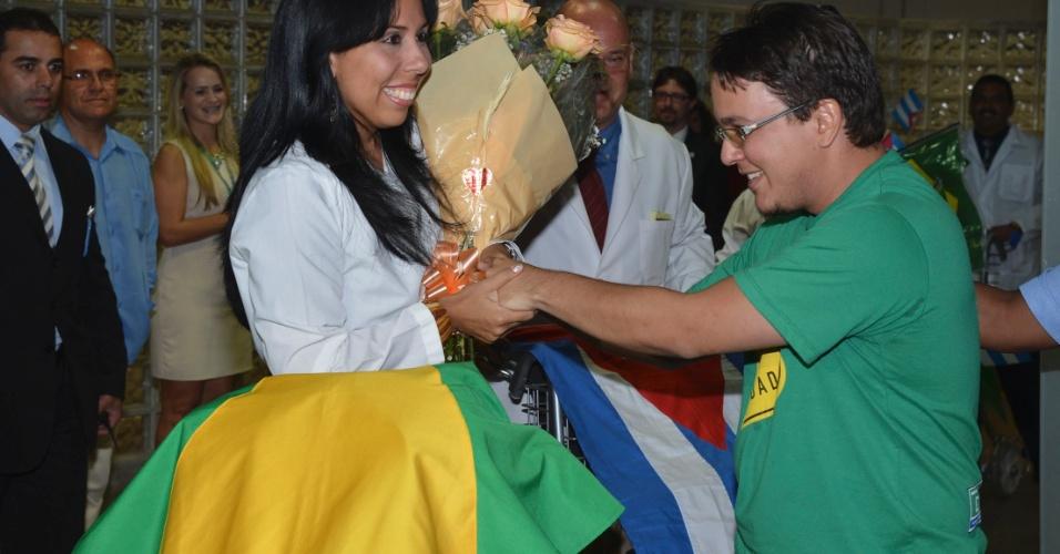 24.ago.2013 - Médica cubana é presenteada por brasileiro durante desembarque no Aeroporto Internacional de Brasília