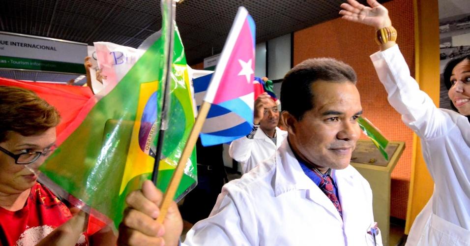 24.ago.2013 - Médico cubano segura bandeira do Brasil e de seu país durante desembarque no Aeroporto Internacional de Brasília
