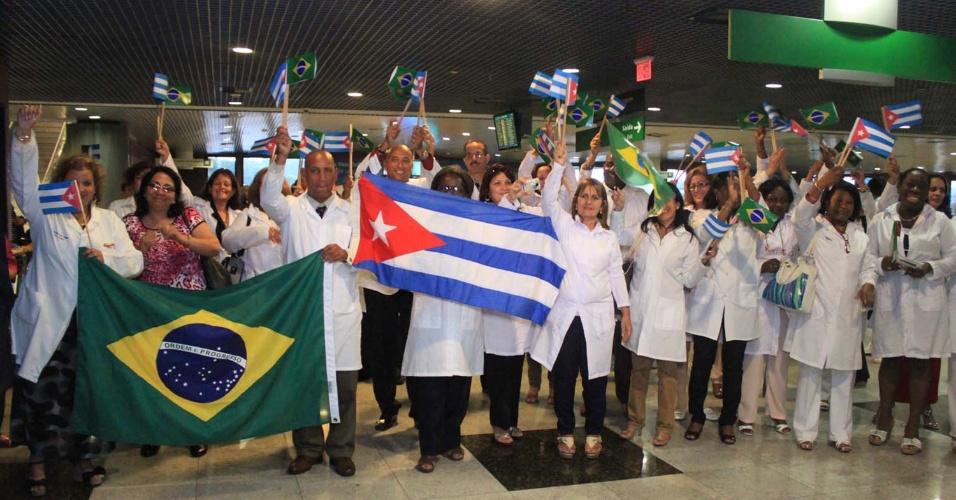 24.ago.2013 - Profissionais exibem as badeiras de Cuba e do Brasil durante a chegada dos primeiros médicos cubanos no Aeroporto Internacional de Recife, em Pernambuco. Eles chegam ao país para integrar o programa Mais Médicos, do governo federal