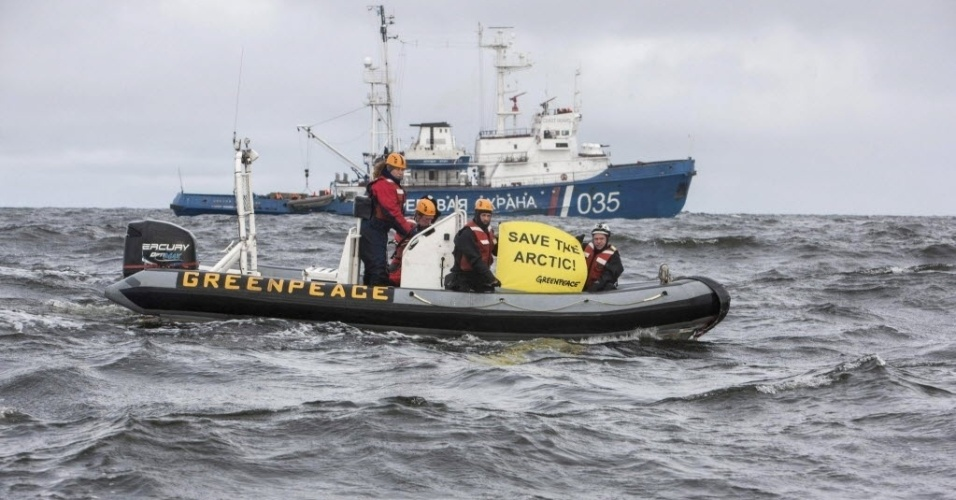 26.ago.13 - Ativistas do Greenpeace protestam nesta segunda-feira (26) em frente a um barco da Guarda Costeira da Rússia que patrulha o Oceano Ártico. A organização havia denuniado a interceptação pelos russos de um navio quebra-gelos seu que estava lá em protesto contra a exploração de petróleo na região