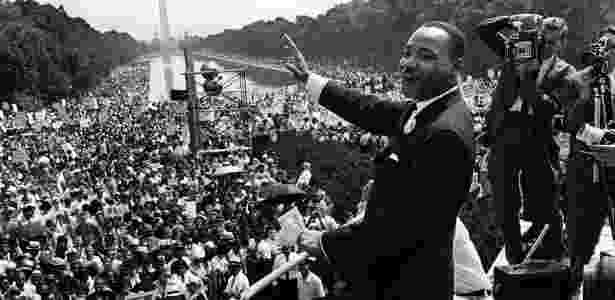 """Martin Luther King acena para a multidão que o acompanha no Memorial Lincoln, em Washington, em 28 de agosto de 1963, por ocasião da Marcha de Washington, realizada por cerca de 200 mil pessoas contra o preconceito e a discriminação racial. Nessa data, King tornou público seu mais famoso discurso, """"I have a dream"""" (Eu tenho um sonho) - AFP - AFP"""