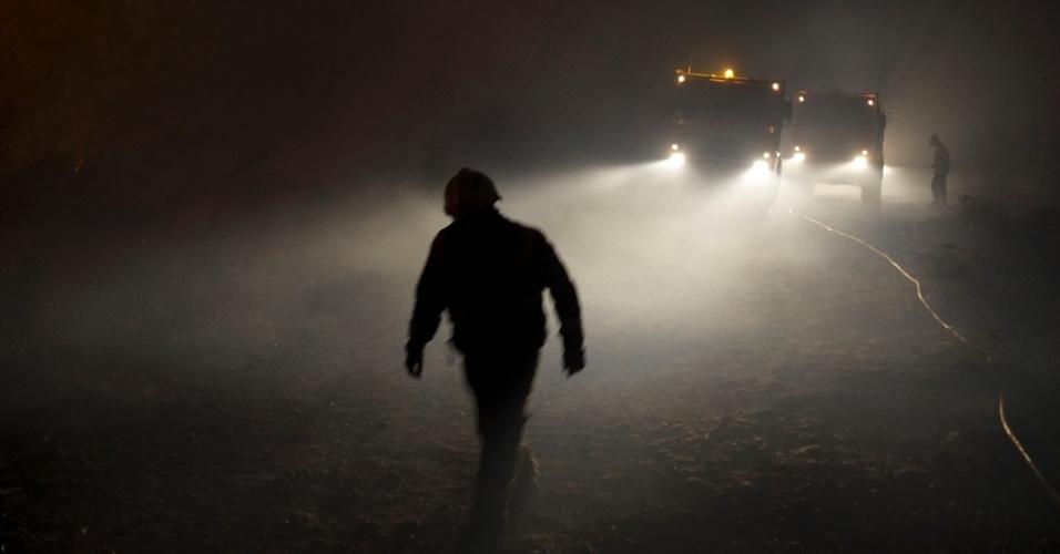 28.ag0.2013 - Membros da Defesa Civil e da Brigada de floresta, no local de um incêndio em Riveira, perto de La Coruna, na Espanha