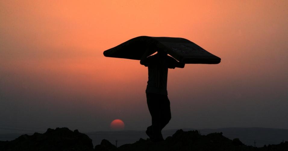 28.ago.2013 - Um homem refugiado sírio-curdo carrega um colchão ao pôr do sol no campo de refugiados Gusik Quru, a leste de Erbil, capital da região autônoma curda do norte do Iraque