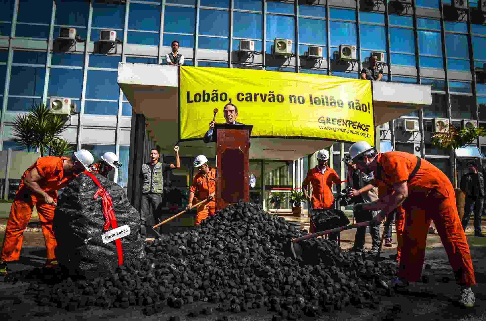 """28.ago.2013 - Ativistas do Greenpeace jogaram 1,5 tonelada de briquete de carvão em frente ao prédio do Ministério de Minas e Energia (MME), na manhã desta quarta-feira (28). Com uma faixa estendida: """"Lobão, carvão no leilão não!"""", o grupo protestou contra o retorno das usinas termelétricas a carvão no Leilão de Energia A-5, marcado para esta quinta-feira (29) - Divulgação"""
