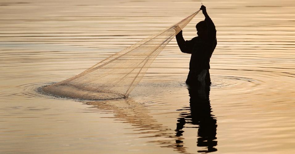28.ago.2013 - Um pescador puxa sua rede em uma lagoa em Trincomalee cerca de 275 quilômetros a leste de Colombo, no Sri Lanka