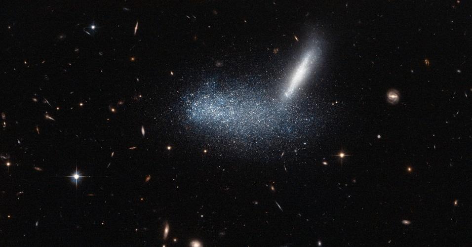 29.ago.2013 - O telescópio Hubble criou uma bela ilusão de ótica ao fotografar duas galáxias entrelaçadas, mas  esses aglomerados de estrelas cintilantes não estão em uma batalha de gigantes, muito menos alinhados no espaço. Tudo não passa de um truque de perspectiva do telescópio espacial: a galáxia anã irregular PGC 16389 (nuvem de estrelas) está em primeiro plano, ao passo que a sua vizinha, a APMBGC 252 125-117, está mais distante