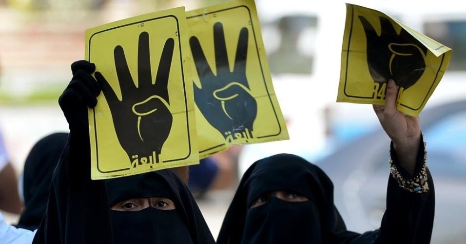 30.ago.2013 - Mulheres participam de protesto no Cairo nesta sexta-feira (30) com cartazes com uma mão fazendo o número quatro. É uma referência à palavra