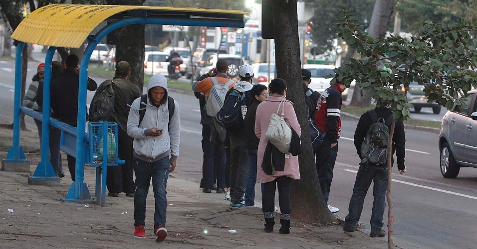 30.ago.2013 - Passageiros aguardam em ponto de ônibus na zona Sul de Porto Alegre, na manhã desta sexta-feira (30). As empresas de ônibus operam com frota reduzida na capital gaúcha, devido aos protestos do Dia Nacional de Mobilização e Paralisação dos rodoviários, metalúrgicos, bancários e petroleiros. Os manifestantes também bloquearam as vias de acesso ao centro da capital e impediram a circulação de trens