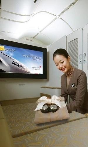 Aeromoça prepara cabine para passageiro da primeira classe da Asiana Airlines. A cabine pode ser completamente fechada e tem, entre outros luxos, monitor de bordo de alta definição de 32 polegadas