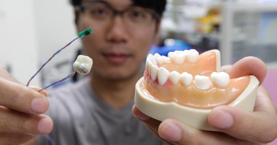 """3.set.2013 - Kelvin Li exibe o protótipo do """"Dente Inteligente"""", que foi desenvolvido no laboratório do Departamento de Ciência Computacional e Engenharia da Informação, na Universidade Nacional de Taiwan, em Taipei. Com um centímetro, o sensor é encaixado no dente artificial com o objetivo de detectar os hábitos diários da pessoa, como mastigação, fumo, bebida, tosse ou excesso de comida. Ele também é capaz de detectar os movimentos da boca - os fios enviam informações aos pesquisadores"""