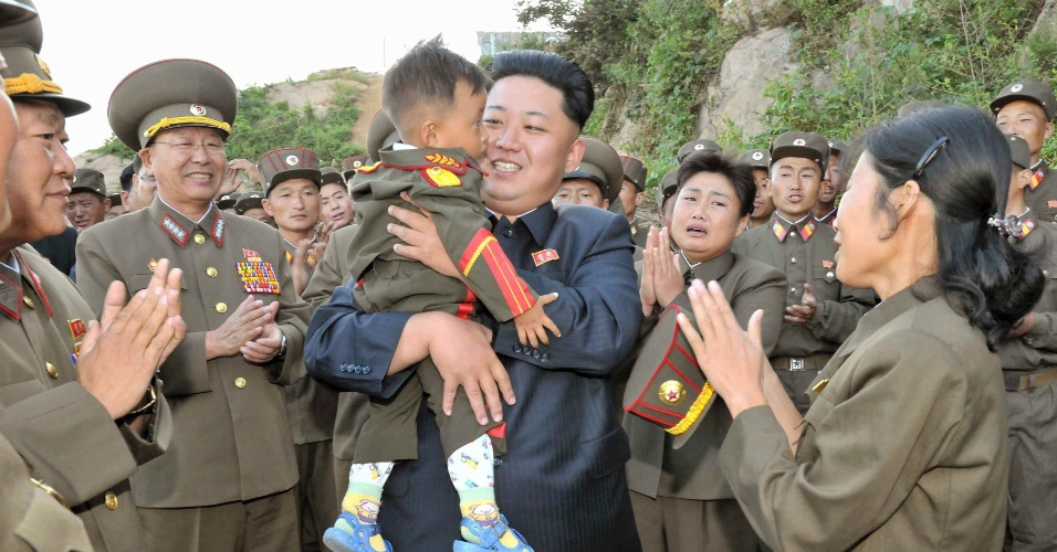 3.set.2013 - Líder norte-coreano Kim Jong-un segura uma criança no colo durante visita a quartel militar em Pyongyang, na Coreia do Norte, nesta terça-feira (3)