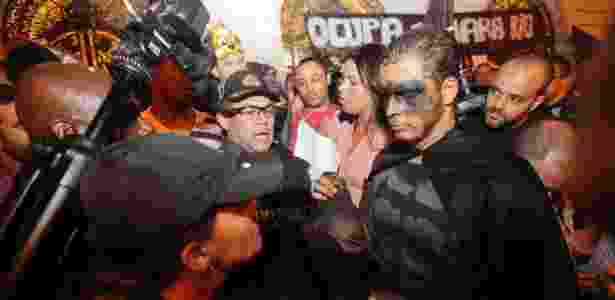 """Manifestante tira máscara e mostra documento a policial militar durante o """"Baile dos Mascarados"""" nas escadarias da Câmara Municipal do Rio  - Bruno Poppe/Frame/Estadão Conteúdo"""