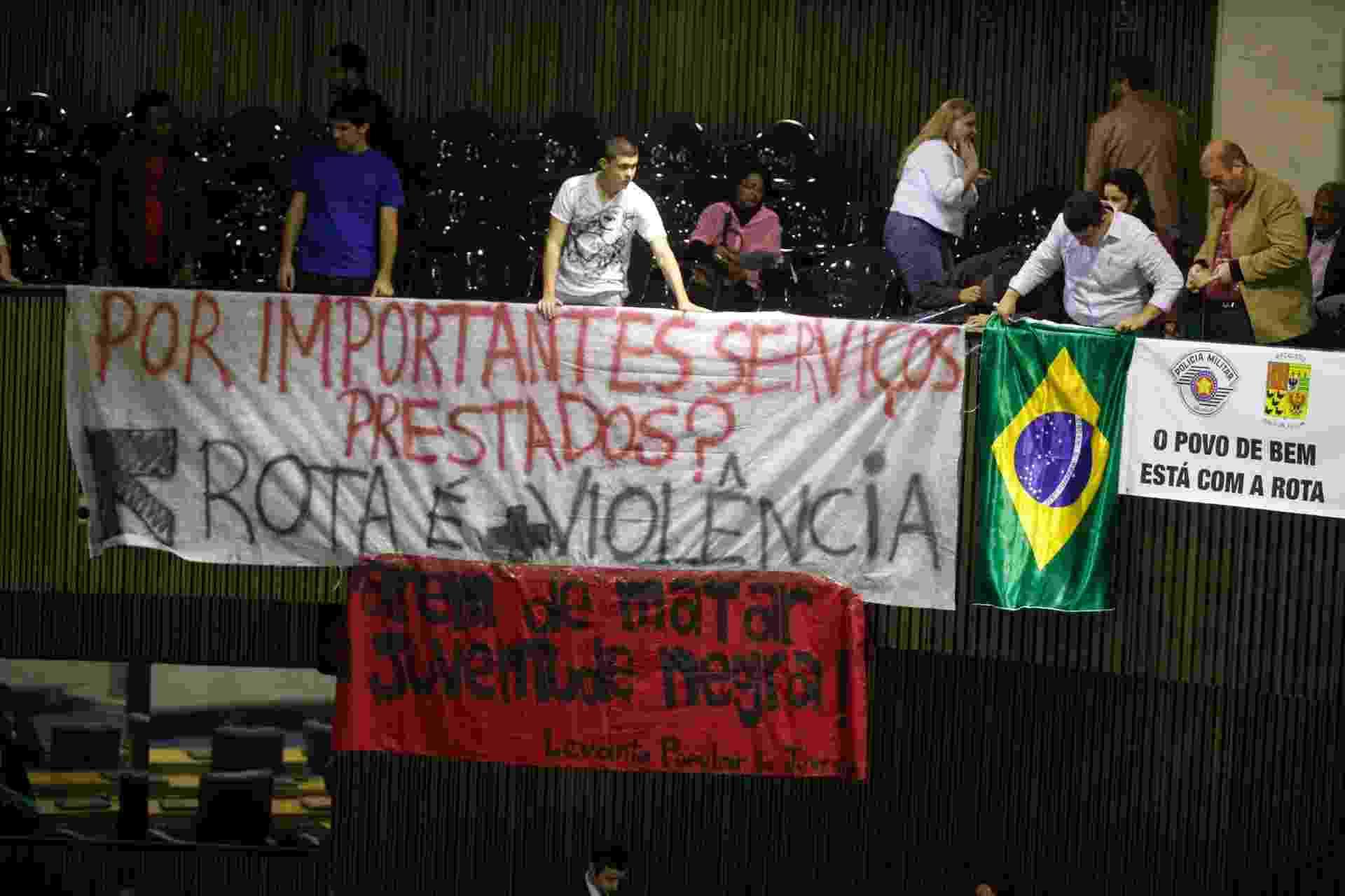 3.set.2013 - Manifestantes colocam faixas dentro do plenário da Câmara Municipal de São Paulo, no centro da capital paulista, para protestar contra a Salva de Prata, uma homenagem à Rota (Ronda Tobias de Aguiar), marcada para a tarde desta terça-feira (3) - Gabriela Biló/Futura Press/Estadão Conteúdo
