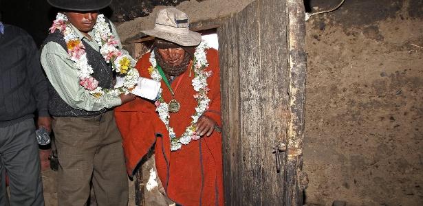 O boliviano Carmelo Flores Laura, que diz ter 123 anos, recebe ajuda para entrar em sua casa - Martin Alipaz/Efe