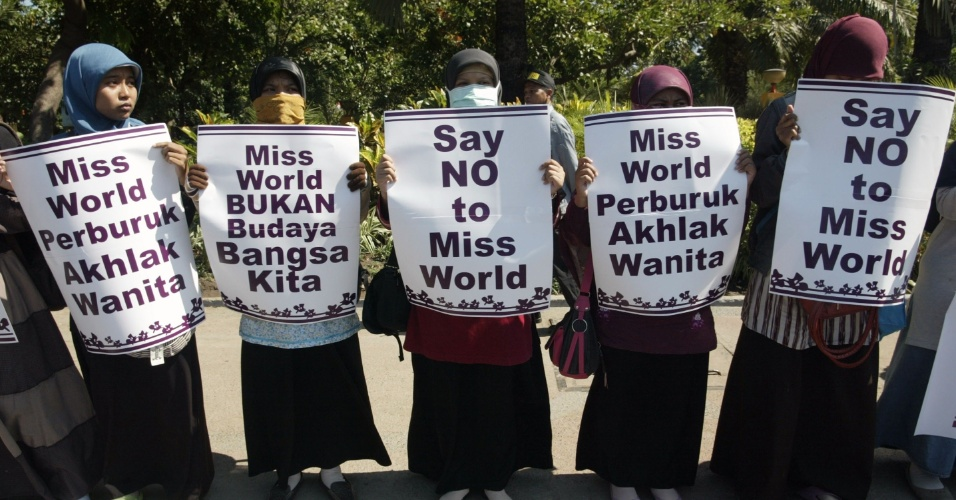 4.set.2013 - Em protesto, mulheres da Indonésia que pertencem a vários grupos conservadores islâmicos seguram placas com dizeres contrários ao Miss Mundo, como