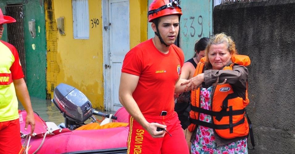 4.set.2013 - Idosa é amparada por bombeiro após resgate no bairro São José, um dos mais atingido pelas chuvas que assolaram João Pessoa (PB) na madrugada desta quarta-feira (4)