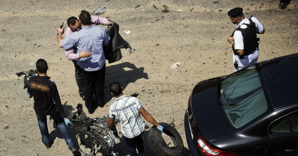 5.set.2013 - Investigadores da polícia se cumprimentam enquanto outros recolhem destroços do local do atentado que visava atingir o ministro do Interior egípcio, Mohammed Ibrahim, nesta quinta-feira (5). Investigação acredita que artefato explosivo foi lançado de um prédio