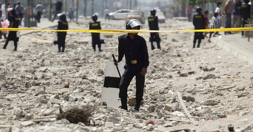 5.set.2013 - Policiais cercam a área do atentado onde, segundo informações do Ministério, homens armados lançaram um explosivo contra os carros da comitiva. No tiroteio que se seguiu, dois terroristas foram mortos