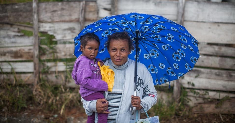 """4.set.2013 - A dona de casa Tatiana Pereira da Silva segura a filha Isabele enquanto anda pelo centro de Marsilac, próximo à UBS Marsilac. Segundo ela, o atendimento da unidade de saúde costuma ser bom. """"Não tenho do que reclamar"""", disse"""