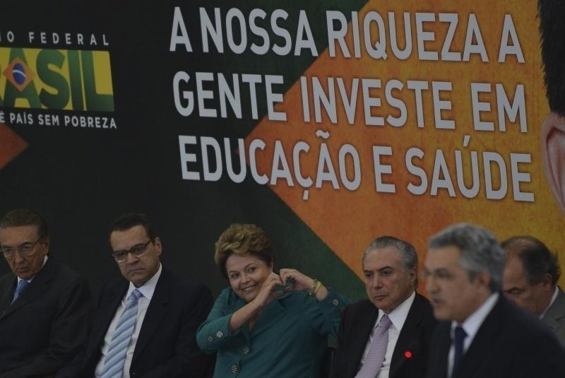 9.set.2013 - A presidente Dilma Rousseff faz um coração com as mãos durante cerimônia que sancionou, nesta segunda-feira (9), em Brasília, uma lei que destina para saúde e educação os fundos obtidos com os royalties da extração do petróleo. Na cerimônia, ela foi acompanhada pela vice-presidente Michel Temer (terceiro, da direita para a esquerda) e por ministros