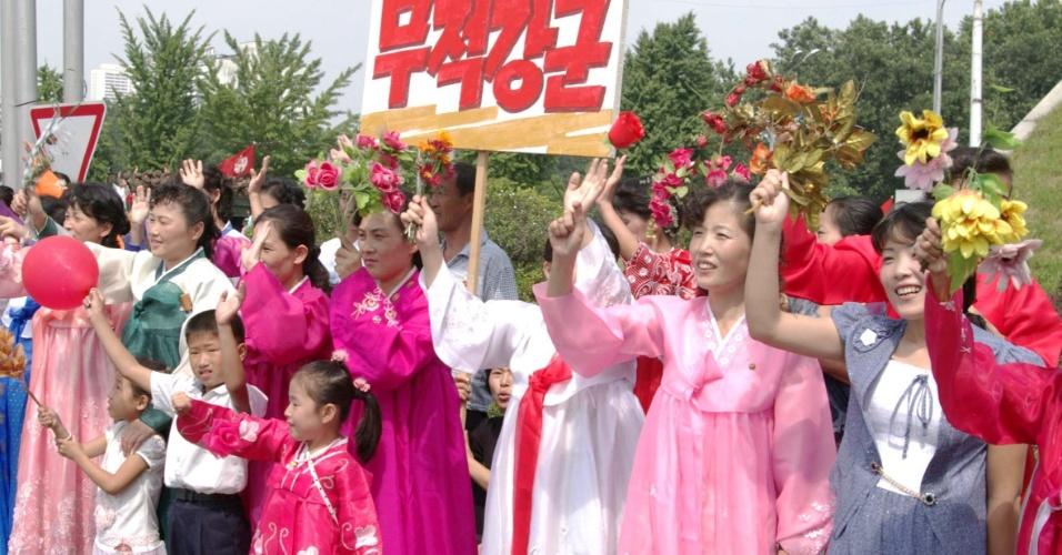 9.set.2013 - Mulheres e crianças norte-coreanas seguram cartazes e flores durante passagem de parada militar para comemorar os 65 anos de fundação da Coreia do Norte, nesta segunda-feira (9), em Pyongyang