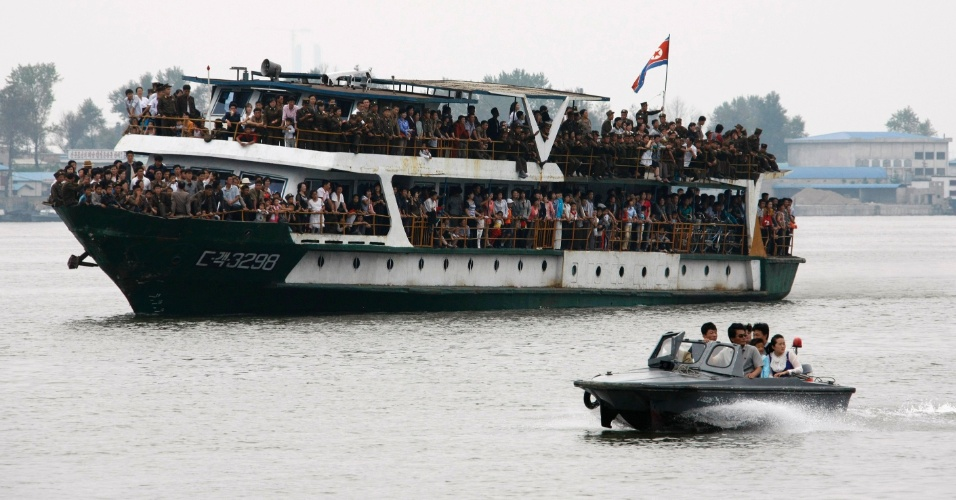 9.set.2013 - Populares e soldados dividem o espaço em um barco que transporta passageiros para a capital da Coreia do Norte, Pyongyang, para acompanhar a parada militar nesta segunda-feira (9), em comemoração aos 65 anos de fundação do país