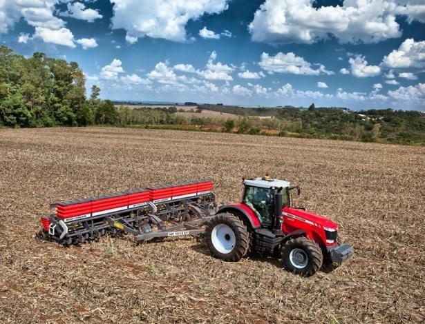 O trator MF8670, com 320 cavalos de potência, usado para carregar equipamentos por grandes extensões de terra, com mais de 10.000 hectares; ele pode carregar até 12.000 kg e é usado no cultivo de grãos; na imagem, o trator carrega uma plantadeira, que é usada para plantar as sementes dentro da terra