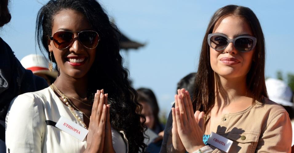 11.set.2013 - Miss Etiópia Genet Tsegay Tesfay (esq.) e a miss Croácia Lana Grzetic posam depois de cerimônia religiosa no templo Besakih, em Karangasem, Bali, Indonésia