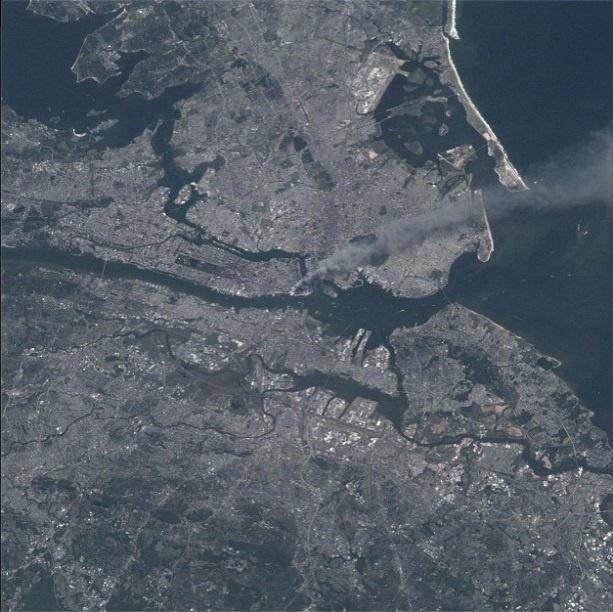 """11.set.2013 - A Nasa (Agência Espacial Norte Americana) divulgou nesta quarta-feira (11) em sua conta na rede social Instagram uma imagem de uma coluna de fumaça subindo da área metropolitana de Nova York, depois que dois aviões se chocaram contra as torres do World Trade Center, na manhã de 11 de setembro de 2001. """"Nossos pensamentos e orações vão para todas as pessoas que estão lá"""", disse o comandante da estação da Expedição 3, Frank Culbertson, após os ataques terroristas, segundo a publicação"""