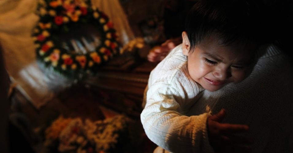 11.set.2013 - Bebê filho de Guillermo Coc, que morreu em um acidente de ônibus no povoado indígena de San Martin Jilotepeque, na Guatemala, na segunda-feira (9), chora durante velório do pai. Quarenta e três pessoas morreram e dezenas ficaram feridas no acidente