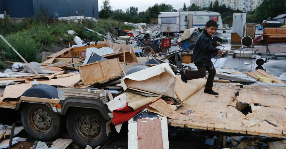 11.set.2013 - Garoto brinca em destroços de um trailer destruído após o despejo de famílias ciganas de seu acampamento ilegal em Lille, na França