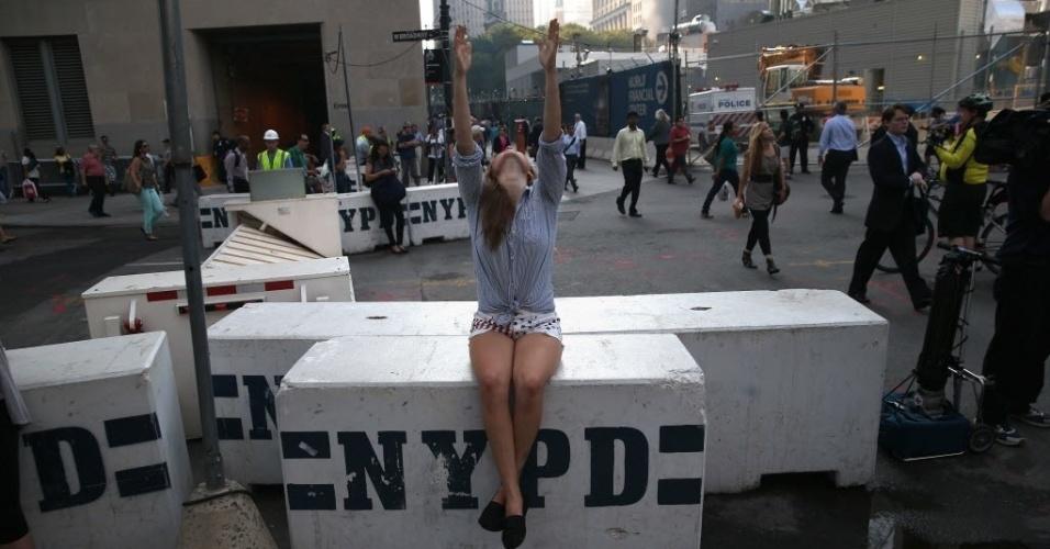 11.set.2013 - Jovem faz oração com os braços erguidos no Marco Zero, em Nova York, onde aconteceram os atentados terroristas de 11 de setembro de 2001, há 12 anos