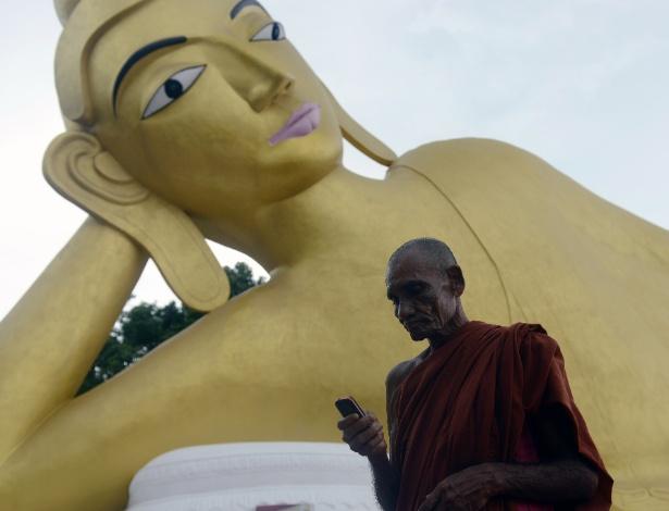 11.set.2013 - Monge budista usa celular em frente a uma estátua de Buda em Ramu a 350 km de Dacca, em Bangladesh