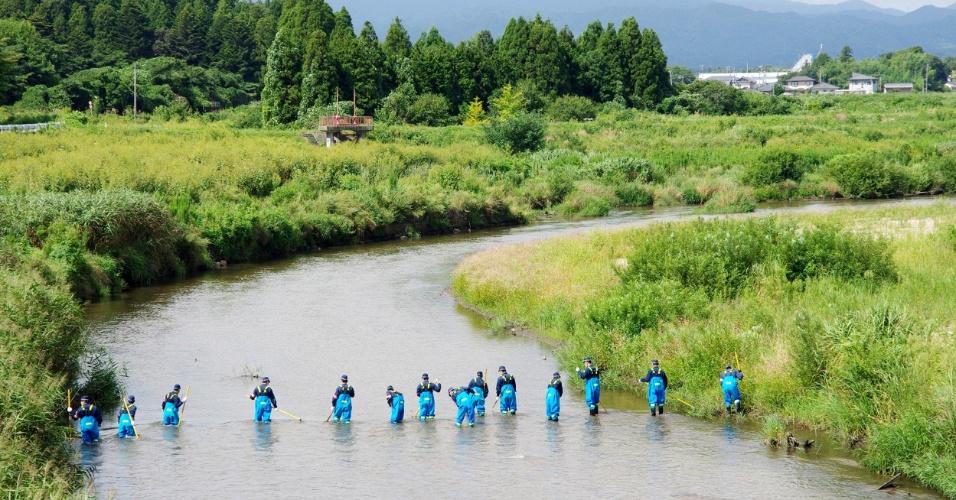 11.set.2013 - Policiais buscam por desaparecidos no rio Namie, perto da usina nuclear de Fukushima, nesta quarta-feira (11), dois anos e meio depois do forte terremoto seguido de tsunami que matou mais de 18 mil pessoas no norte do Japão