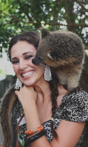12.set.2013 - Animal se enrosca no pescoço da miss Peru Elba Fahsbender Merino durante visita a safári em Bali, Indonésia