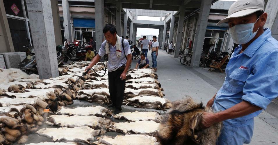 13.set.2013 - Funcionário de uma das empresas de Chongfu usa spray de água sobre as peles em uma loja de um mercado da cidade, nesta sexta-feira (13). Técnica é feita antes de embalar as peles para exportação