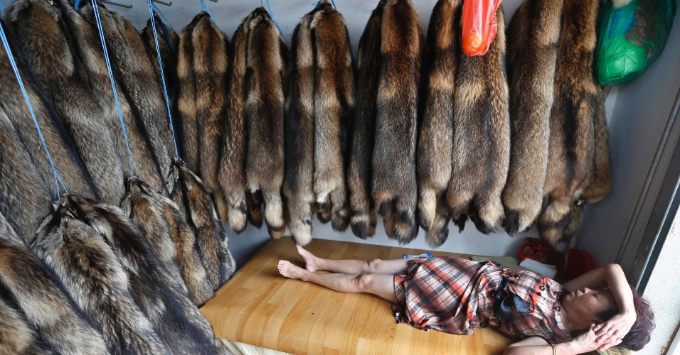 13.set.2013 - Vendedora dorme em pequena loja de casacos em um mercado especializado em Chongfu, na China, nesta sexta-feira (13). Peças saem do país por um preço bem abaixo dos que são praticados na Europa e nos Estados Unidos