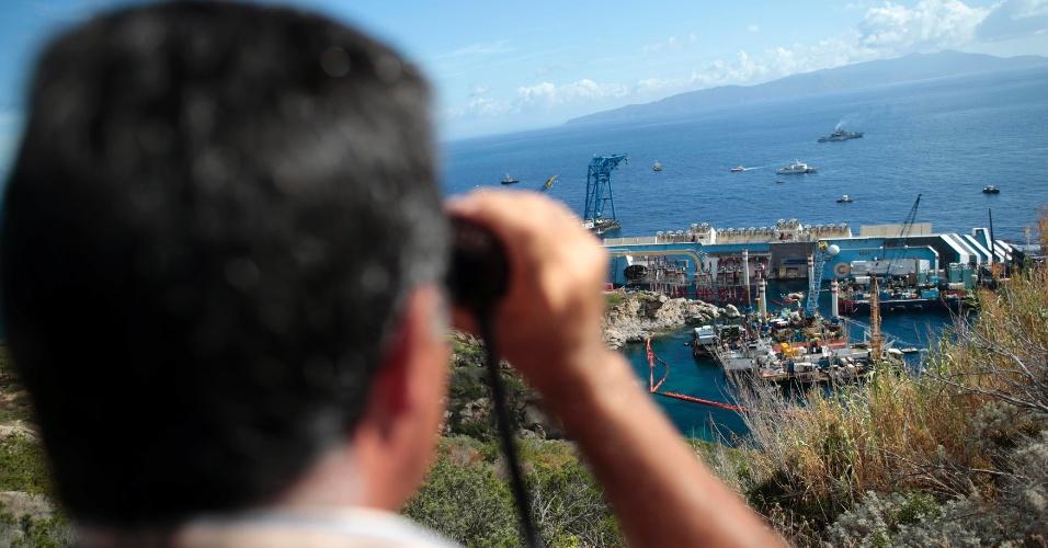 16.set.2013 - Com um binóculo, homem observa, da costa da ilha de Giglio, na Itália, os trabalhos para içar o navio Costa Concórdia, nesta segunda-feira (16). Empresas começaram os trabalhos às 4h (horário de Brasília) e a previsão é que seja concluído em 12 horas