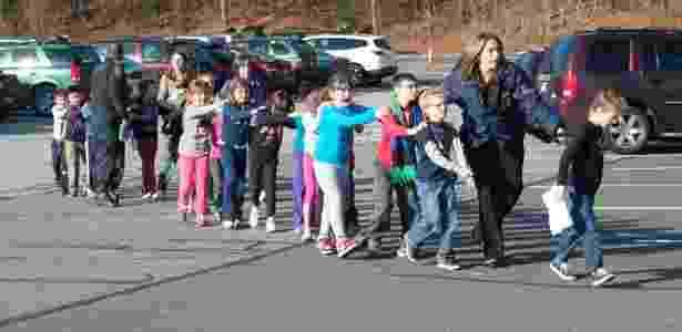 Dezembro de 2012: Adam Lanza, 20, assassinou 20 crianças e seis adultos na escola primária de Sandy Hook em Newtown, Connecticut. Na foto, policiais escoltam alunos para fora da escola - 14.12.2012 - Shannon Hicks/Newtown Bee/Reuters - 14.12.2012 - Shannon Hicks/Newtown Bee/Reuters