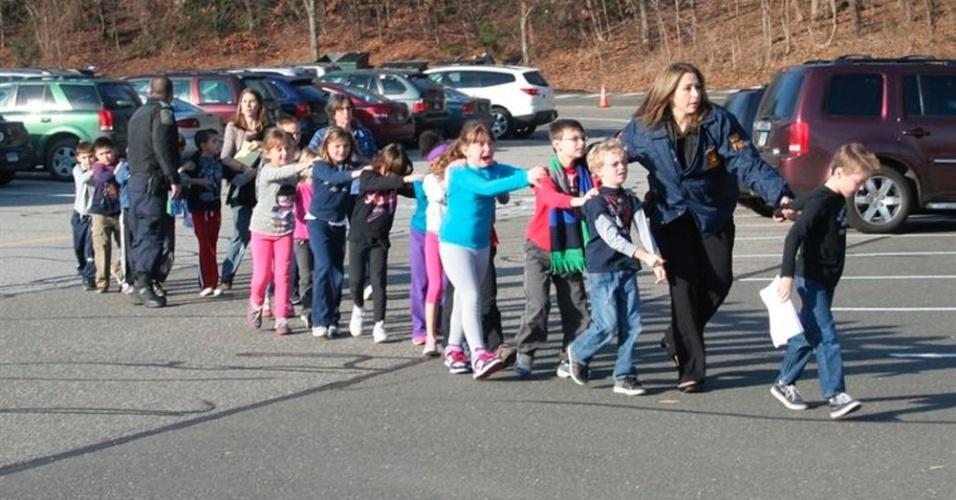 16.set.2013 - Dezembro de 2012: Adam Lanza, 20, assassinou 20 crianças e seis adultos na escola primária de Sandy Hook em Newtown, Connecticut. Na foto, policiais escoltam alunos para fora da escola