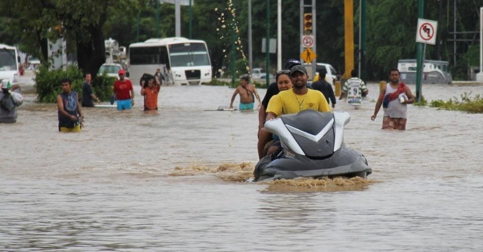 16.set.2013 - Homem conduz moto por via inundada em Acapulco, no México, nesta segunda-feira (16). Pelo menos trinta pessoas morreram desde o último fim de semana e há pelo menos 200 mil pessoas afetadas pelo impacto simultâneo furacão Ingrid e a tempestade tropical Manuel, um fenômeno raro que não se presenciava havia meio século