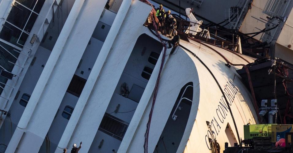 16.set.2013 - Operários de duas empresas especialicadas fazem os últimos preparativos para começar o içamento do navio Costa Concórdia, nesta segunda-feira (16), na ilha de Giglio, na Itália. A operação, sem precedentes na história, vai levantar o gigantesco transatlântico que, há 21 meses, naufragou causando a morte de 32 pessoas