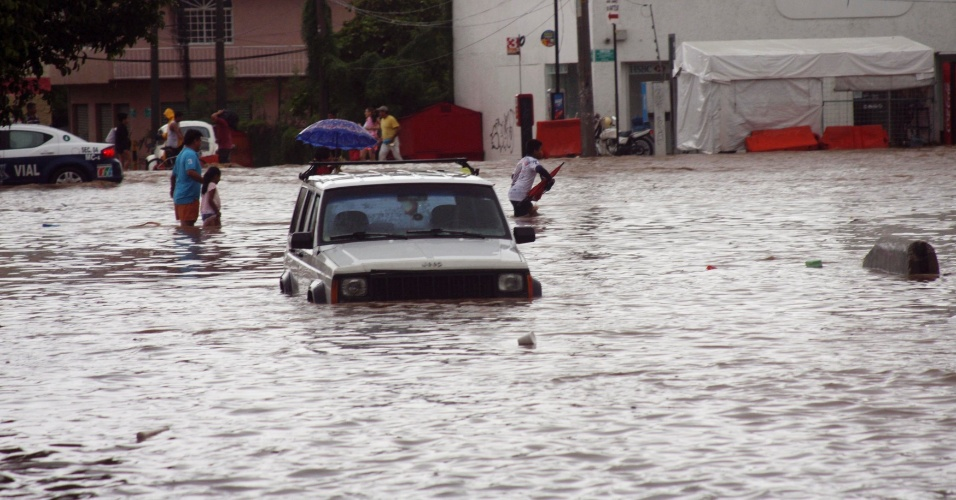 16.set.2013 - Pessoas atravessam rua alagada de Acapulco, entre carros submersos, retirando objetos pessoais das casas, nesta segunda-feira (16), após passagem do furacão Inngrid e a tempestade tropical Manuel. Número de mortos sobre para 21