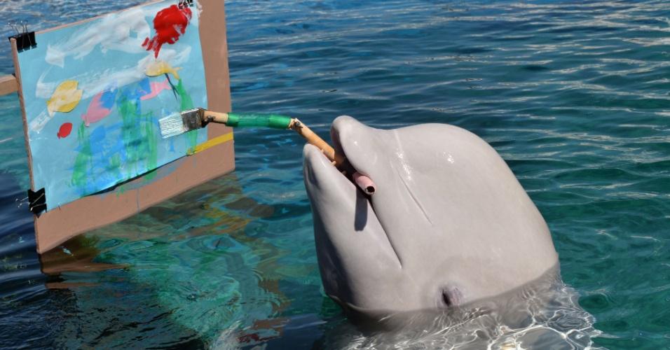 Beluga (baleia-branca) pinta quadro com pincel especial nesta terça-feira (17) em parque aquático de Yokohama, no Japão